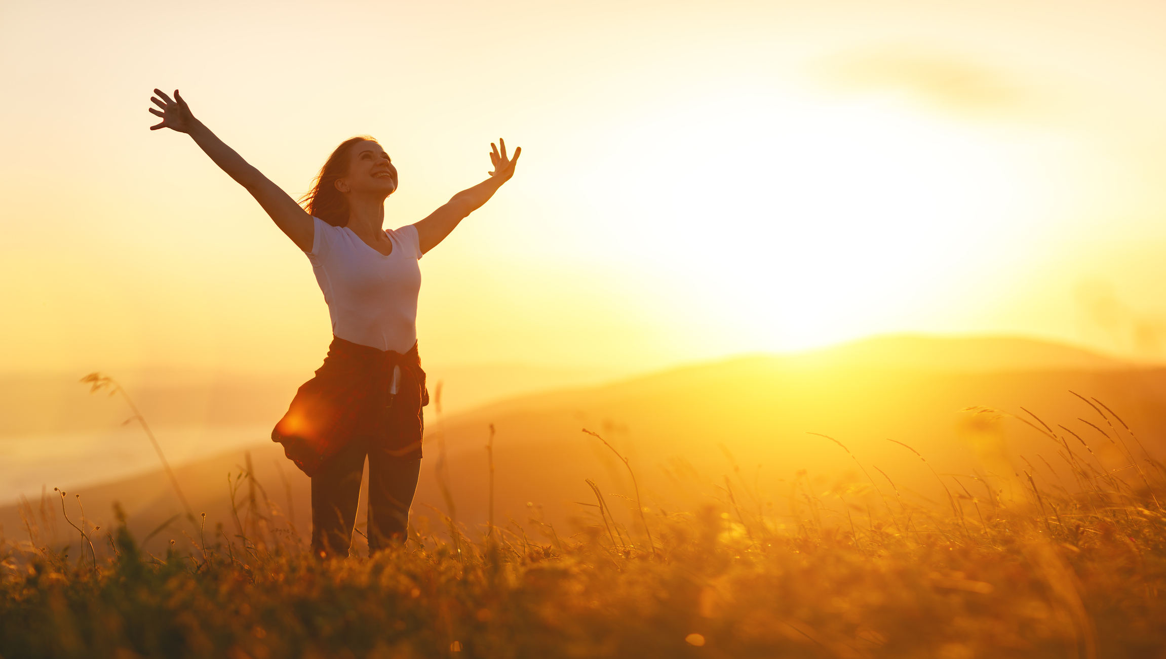 Happy woman   on the sunset in nature in summer with open hands